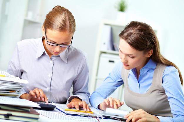 Employees using calculators Free Photo
