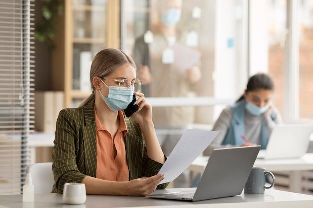 Сотрудники в масках для лица в офисе Premium Фотографии