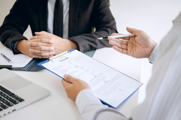 Employer arriving for a job interview, businessman listen to candidate answers explaining about his profile and colloquy dream job, manager sitting in job interview talking in office Premium Photo