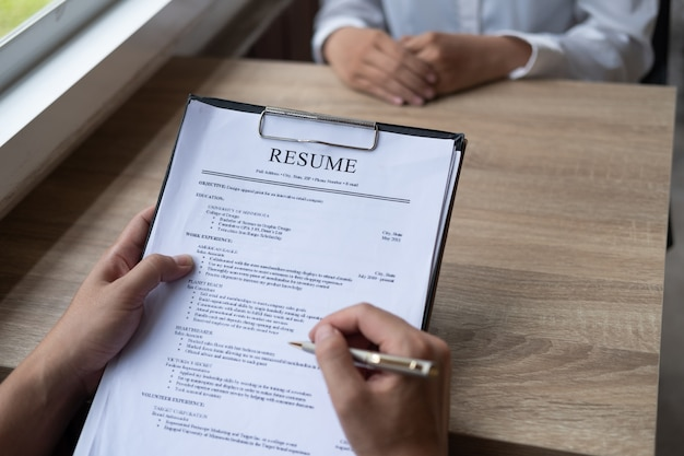Employer interviewing a young male job seeker sitting at a table reading his cv viewed fro Premium Photo
