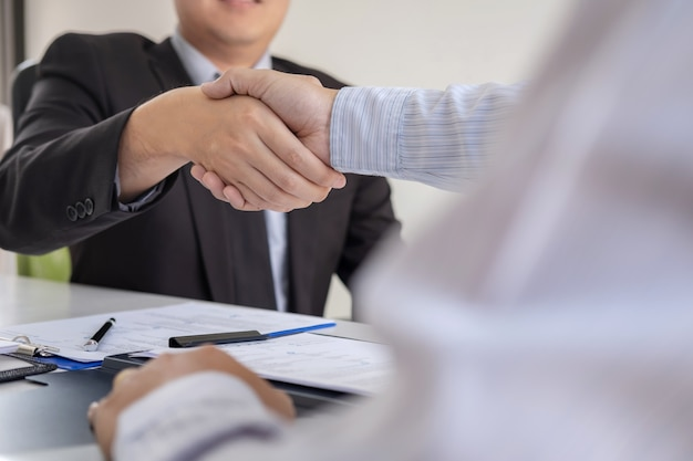 Employer in suit and new employee shaking hands after negotiation and interview placement Premium Photo