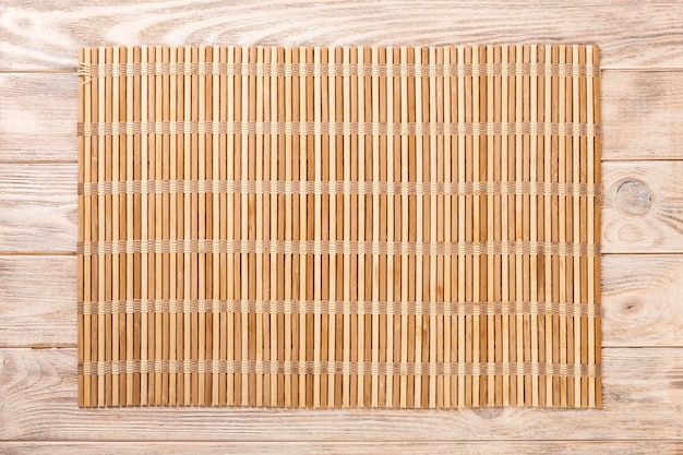 Empty asian food background. brown bamboo mat on wooden background top view with copy space flat lay Premium Photo