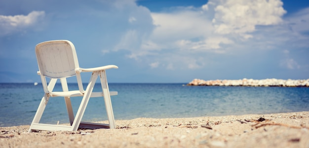 Empty beach chair by the sea with stormy clouds in the background Premium Photo