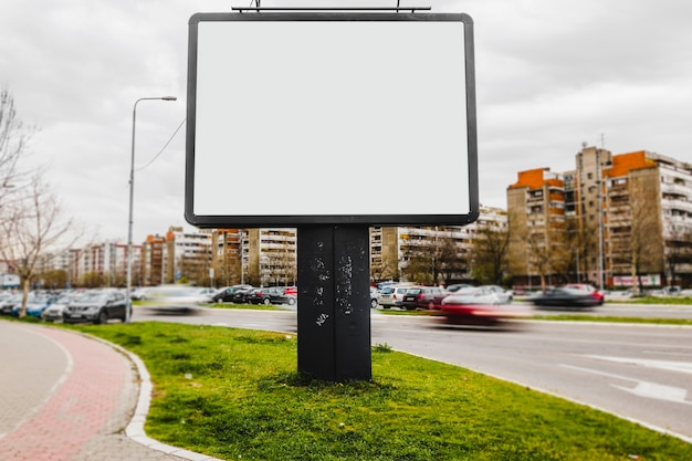 An empty billboard in the middle of city road Free Photo