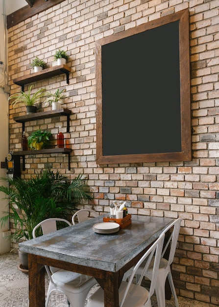 Empty black board on brick wall and dinning table in below. Premium Photo