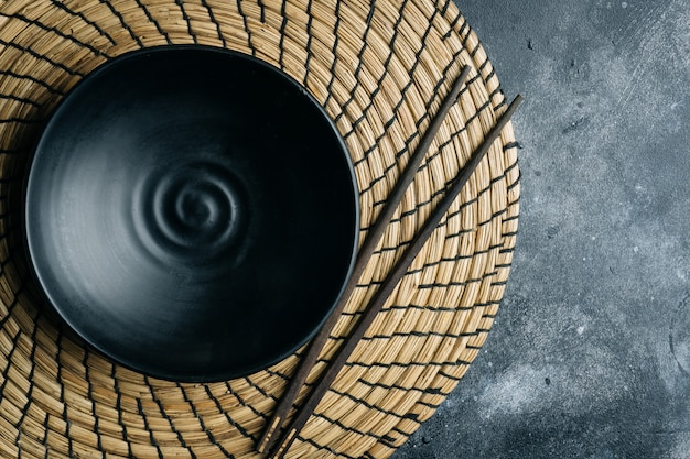 Empty black bowl (ceramic handmade) with chinese chopsticks on a gray stone Premium Photo