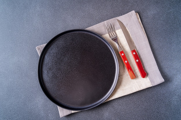 Empty black and cutlery plate over napkin on brown wooden table top view, copy space for text. Premium Photo