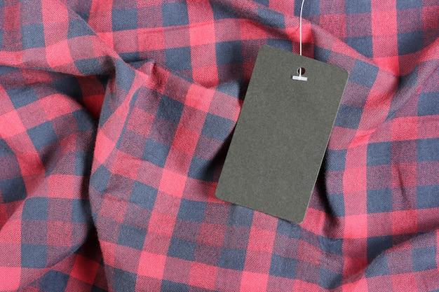赤い市松模様の生地、トップビューで空の黒いラベル Premium写真