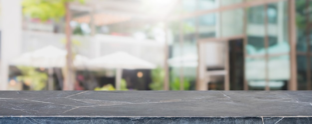 Empty black marble stone table top and blurred restaurant exterior banner background Premium Photo