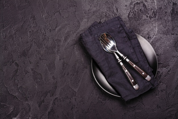 Опорожните черную плиту и silverware на темном каменном backgroun. вид сверху Premium Фотографии