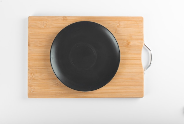 An empty black saucer on a wooden board Free Photo
