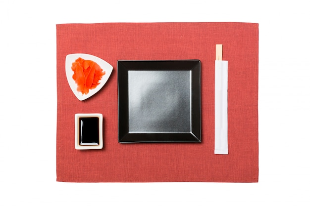 Empty black square plate with chopsticks for sushi, ginger and soy sauce on red napkin Premium Photo