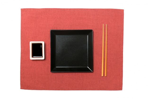 Empty black square plate with chopsticks for sushi and soy sauce on red napkin Premium Photo