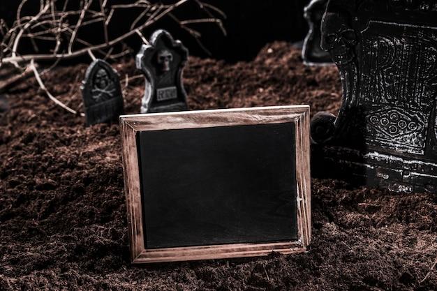 Emptyblackboard on halloween graveyard Free Photo