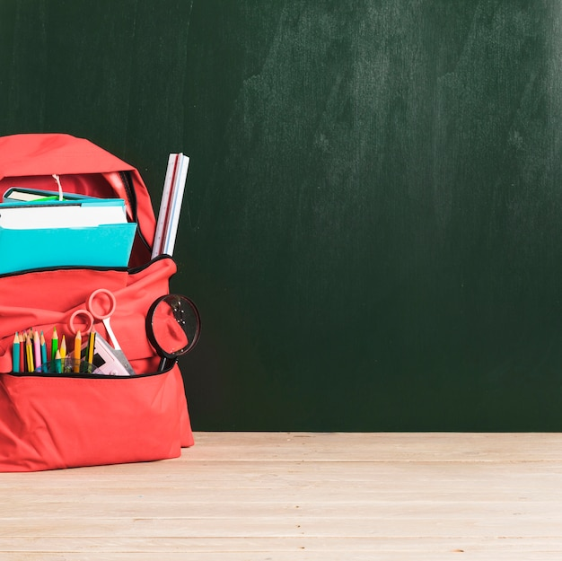 Empty blackboard and red school backpack with supplies Free Photo