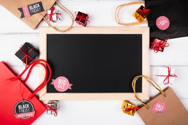 Empty blackboard surrounded by shopping bags Free Photo