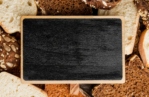 Empty blackboard surrounded by slices of bread Free Photo