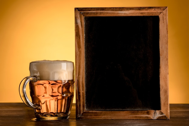 Empty blackboard with glass of beer on wooden table Free Photo
