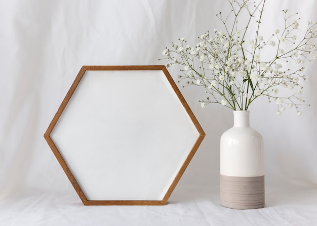 Empty blank photo frame with flower vase in front of white curtain Free Photo