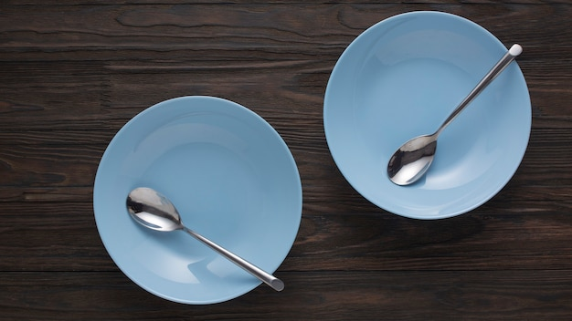 Empty blue dishes with spoons on a wooden table. top view Premium Photo