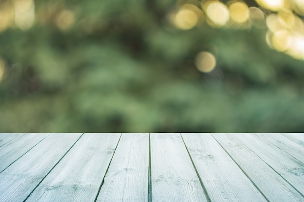 Empty blue wooden table with blurred city park on background. concept party, products, spring background Premium Photo
