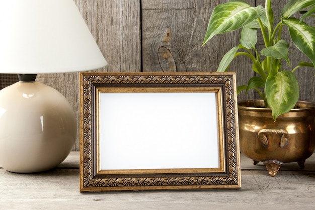 Empty brass picture frame on wooden background. Premium Photo