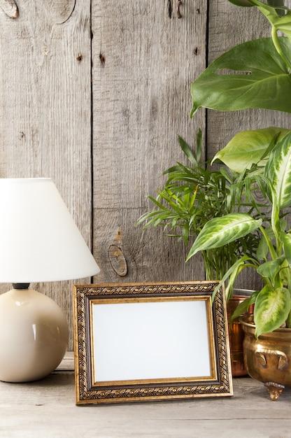 Empty brass picture frame on wooden background. Premium Photo