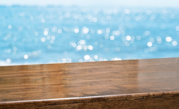 Empty brown glossy wood table top with blur sky and sea boekh background Premium Photo