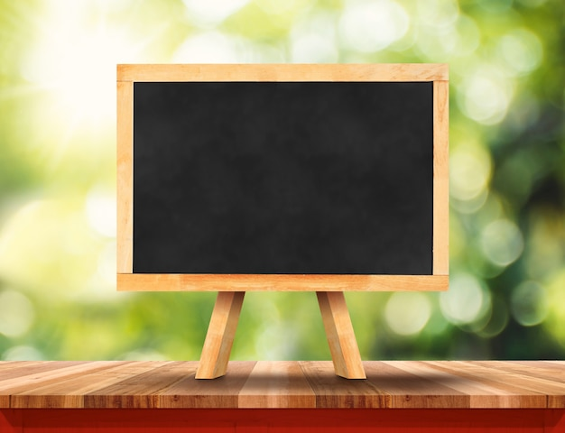 Empty brown wood table top with sun and blur green tree bokeh background Premium Photo