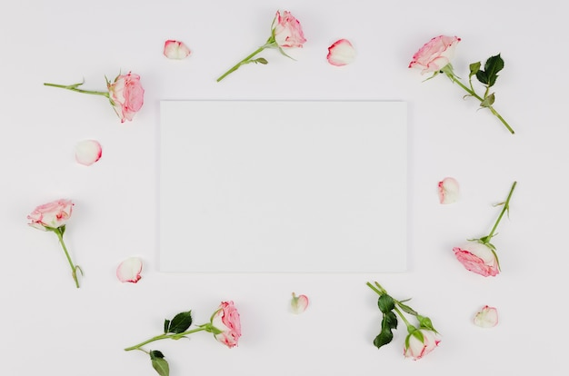 Empty card surrounded by delicate roses Free Photo