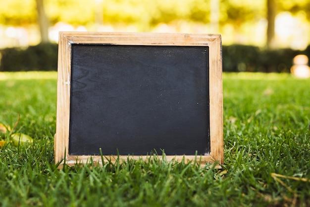 Empty chalkboard on green grass Free Photo