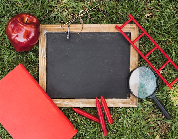 Empty chalkboard near stationery, glasses and apple on grass Free Photo