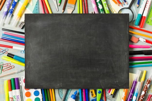 カラフルな背景の空の黒板 Premium写真