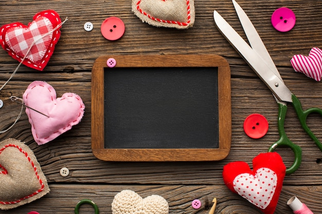 Empty chalkboard surrounded by haberdashery accessories Free Photo