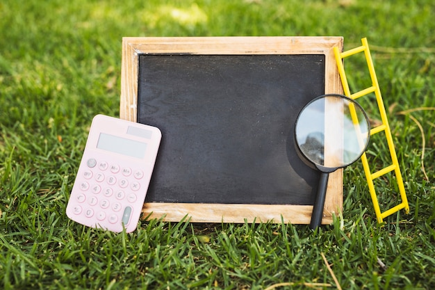 Empty chalkboard with calculator and magnifier on grass Free Photo