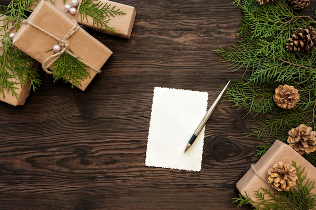 Empty christmas card, gifts boxes, branch and fir cones on wood Premium Photo