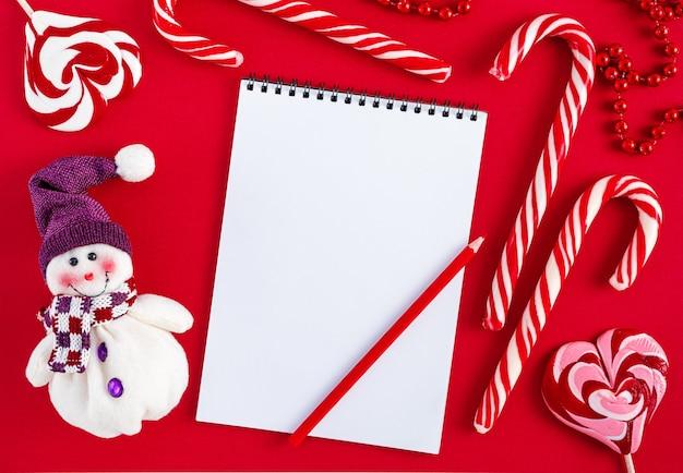 Пустой рождественский список желаний пустой с конфетами и снеговиком на красном фоне Premium Фотографии