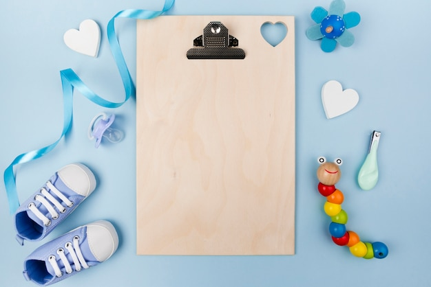 Empty clipboard and baby shoes Free Photo