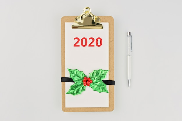 Empty clipboard notebook with christmas decor and pen on white Premium Photo