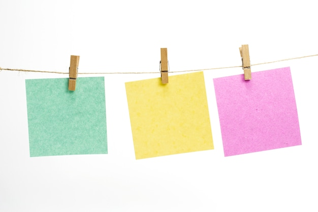 Empty colored paper sheets for notes, frames that hang on a rope with clothespins and isolated on white. Free Photo