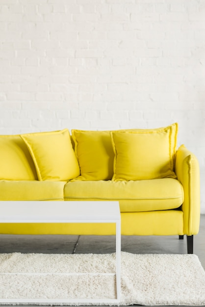 Empty cozy yellow sofa and white table on carpet against white wall Free Photo