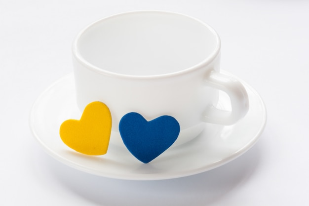 Empty cup and saucer with hearts Premium Photo