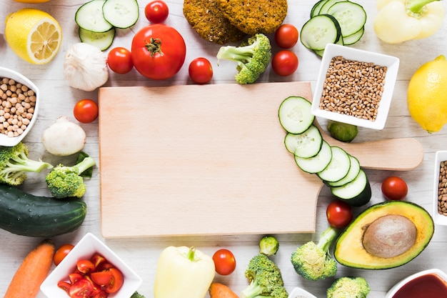 Empty cutting board surrounded by veggie food Free Photo