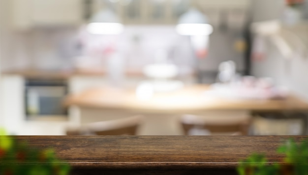Пустой темно-коричневый деревянный стол с размытой домашней кухней с размытия листьев переднего плана Premium Фотографии