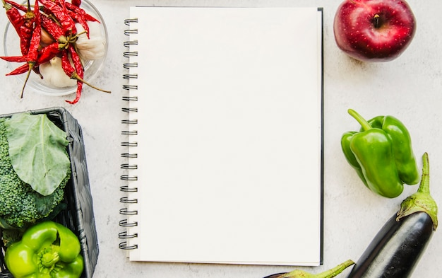 Empty diary and fresh vegetables on white background Free Photo