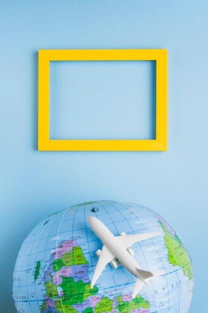 Empty frame, globe and plane Free Photo