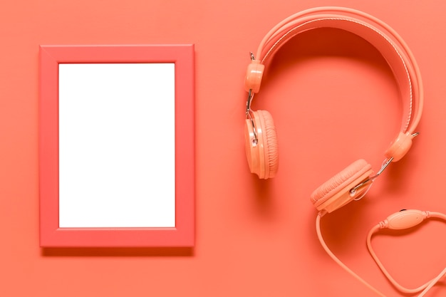 Empty frame and pink earphones on colored surface Free Photo