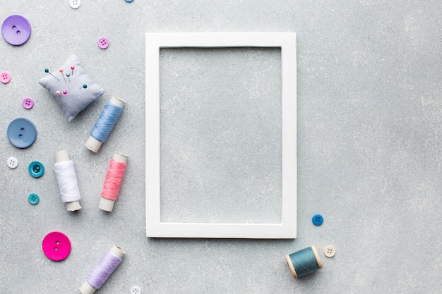 Empty frame surrounded by haberdashery accessories Free Photo