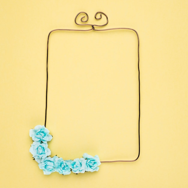 An empty frame with decorative flower on yellow background Free Photo