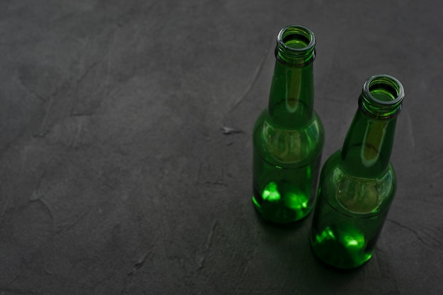 Empty glass bottles on black surface Free Photo